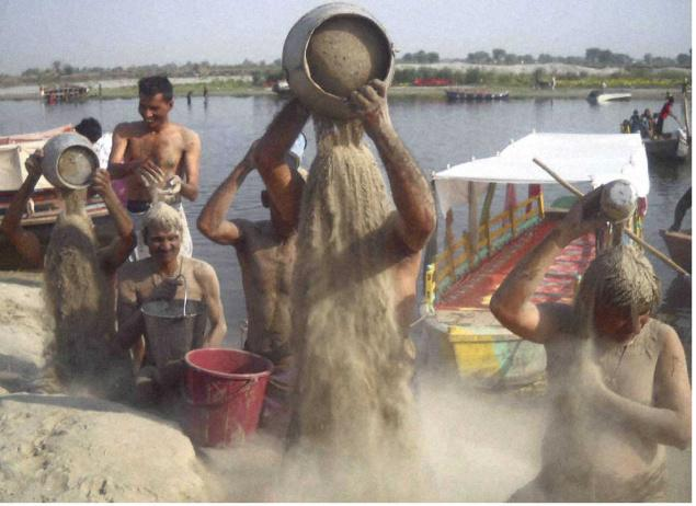 Against pollution: Devotees bathe with sand in protest against pollution of the Yamuna river on the eve of Ganga Dussehra festival at Vrindavan on Sunday.