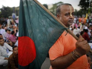 A Hindu monk holds a Bangladesh national flag as they block a street during a protest in Dhaka September 10, 2013. Hundreds of Hindu devotees from across the country blocked a street protesting the move to pass the Debottor (endowment) Property Management Act, 2013. The cabinet approved the draft Debottor (endowment) Property Management Act, 2013 for regulating management, development and transfer of 'Debottor' (endowed) properties donated to Hindu places of worship on June 3. The protestors claimed the proposed law was against the rules and culture of Hindu religion, local media reported. REUTERS/Andrew Biraj (BANGLADESH - Tags: POLITICS RELIGION CIVIL UNREST)
